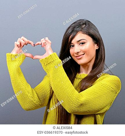 Beautiful happy woman holding heart in hands against gray background