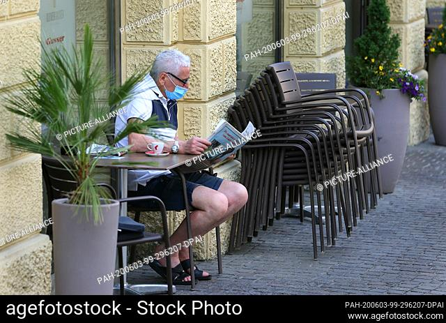 03 June 2020, Italy, Brixen: A man wearing a mouth guard reads a newspaper in a street cafe. Since 03.06.2020, EU citizens are allowed to enter Italy again...