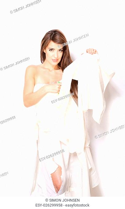 attractive woman in ripped wedding dress on white background