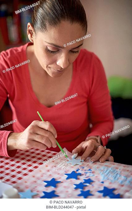 Hispanic woman painting stars at table