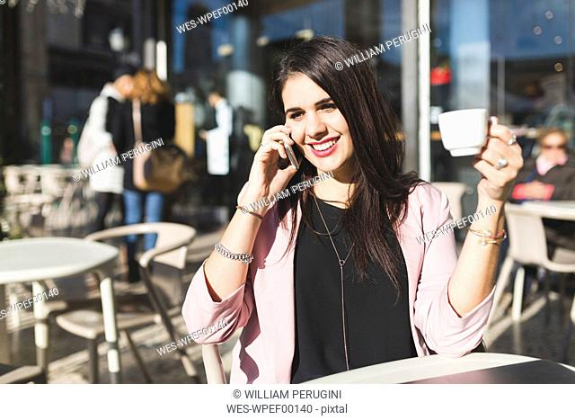 Smiling young businesswoman on cell phone at an outdoor cafe