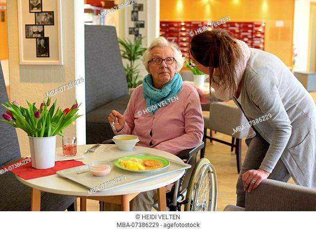 Old woman eating in a retirement home with a nurse