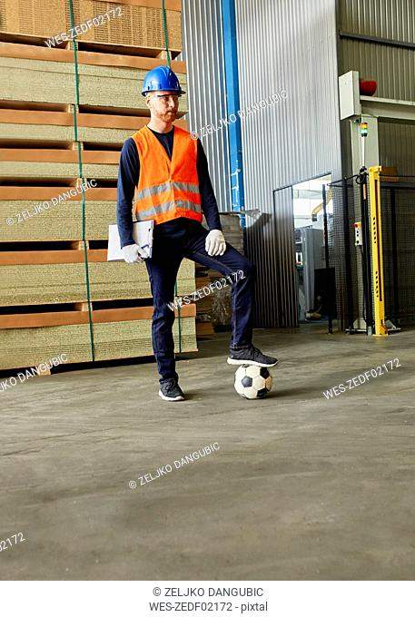 Worker standing in factory warehouse with football