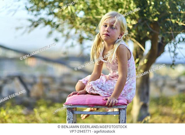 young infant girl sitting on chair outside in nature garden. Australian ethnicity. During holiday stay in Hersonissos, Crete, Greece