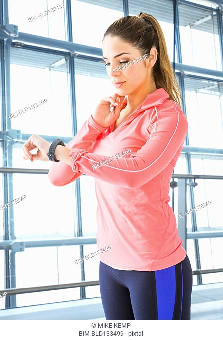 Mixed race woman checking pulse in gym