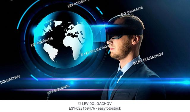 technology, people, cyberspace, mass media and augmented reality concept - young businessman with virtual headset or 3d glasses and earth hologram over black...