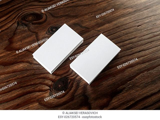 Blank business cards with soft shadows on wooden background. Mock-up for branding identity. Top view