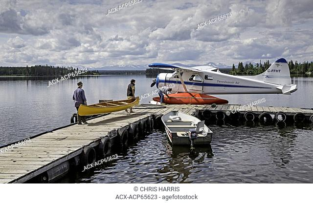 Loading canoes onto docked float plane, Coast Mountains, British Columbia, Canada