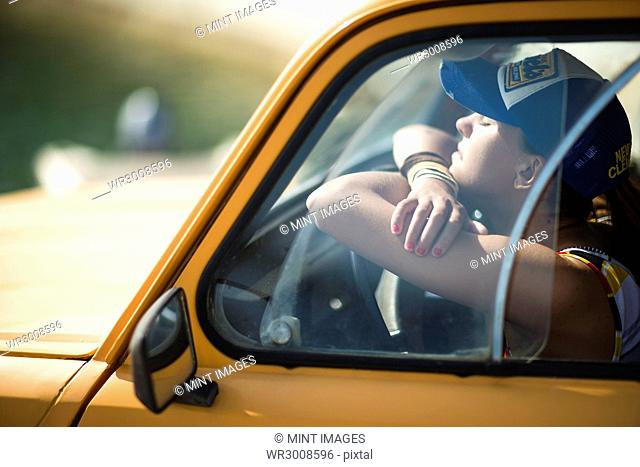 Young woman sitting in the cab of a car