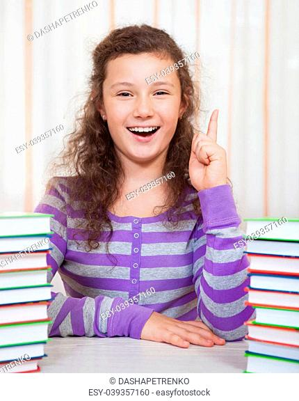 Little brunette smiling girl with piles of books