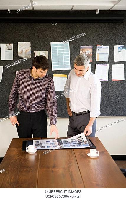 Businessmen looking at portfolio