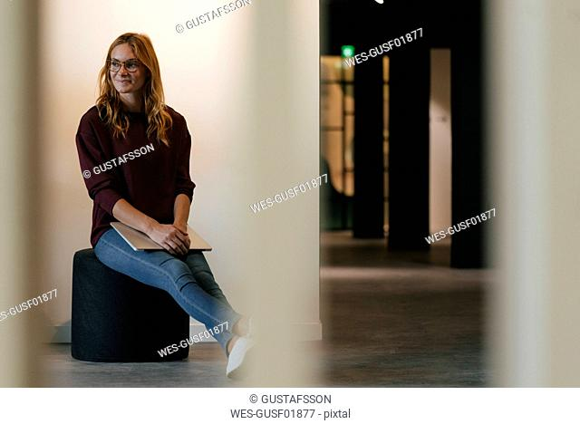 Smiling businesswoman sitting on stool holding laptop