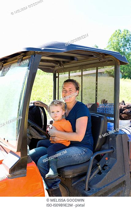 Portrait of female farmer and toddler daughter in truck on free range organic farm