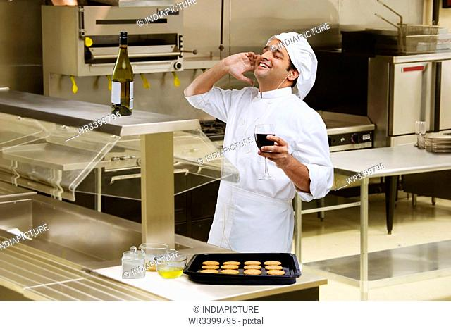 Chef listening to music while holding a glass of wine