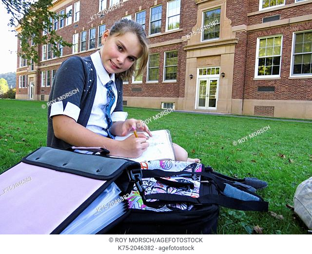 Girl studying on lawn outside school