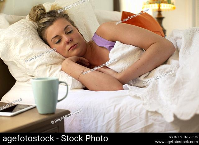 Young woman in her bed debating getting out of bed, smartphone and coffee mug sitting on bedside table