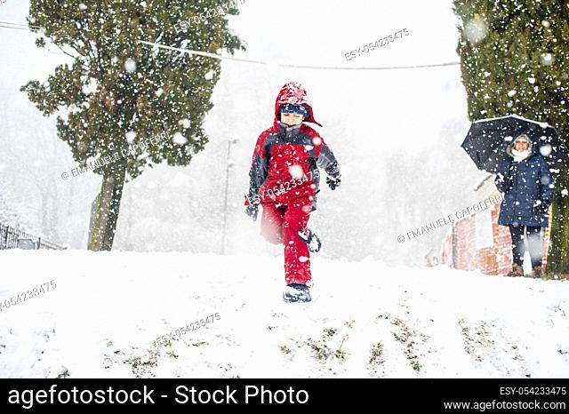 Child playing in the snow jumping from a descent