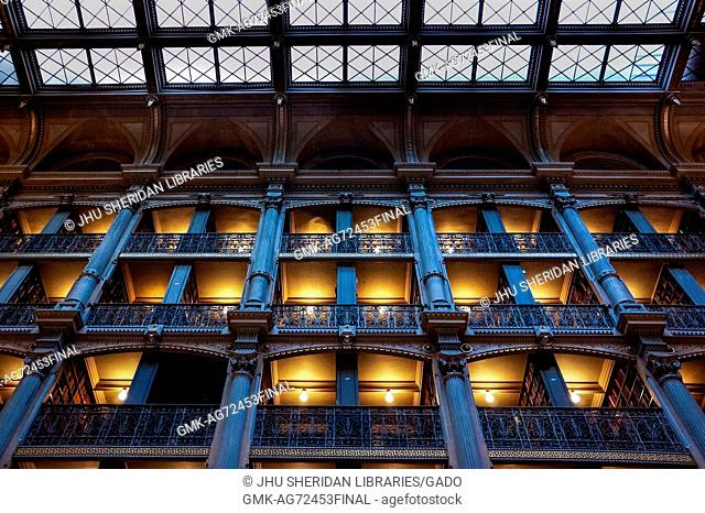 A low-angle shot of the levels of the George Peabody Library, a research library for Johns Hopkins University, with cast iron railings and exposed glowing light...