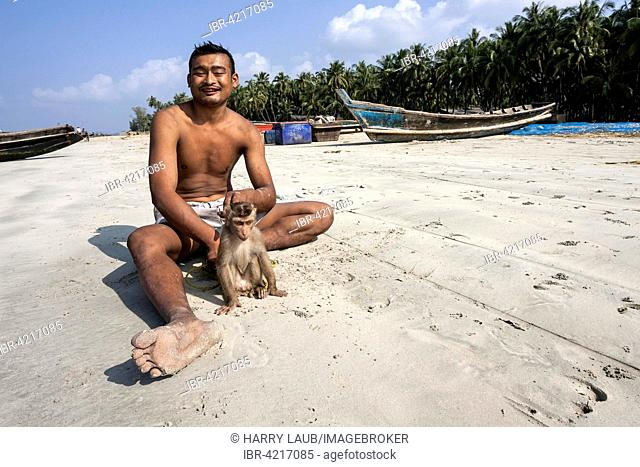 Local man sitting with a monkey on a leash on the beach of the fishing village Ngapali, fishing boats behind, Thandwe, Rakhine State, Myanmar