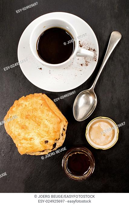 sweet british raisin scone and a glass filled with honey, cup hot instant coffee also small spoon on slate