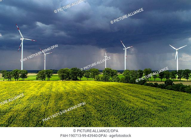 13 July 2019, Brandenburg, Petersdorf: Thunderstorm clouds are moving over the landscape with a field of sunflowers in the Oder-Spree district (aerial...