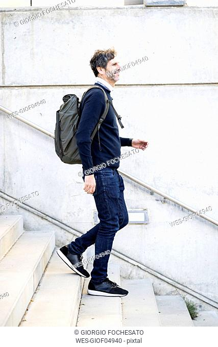 Smiling mature man with a backpack walking down stairs in the city