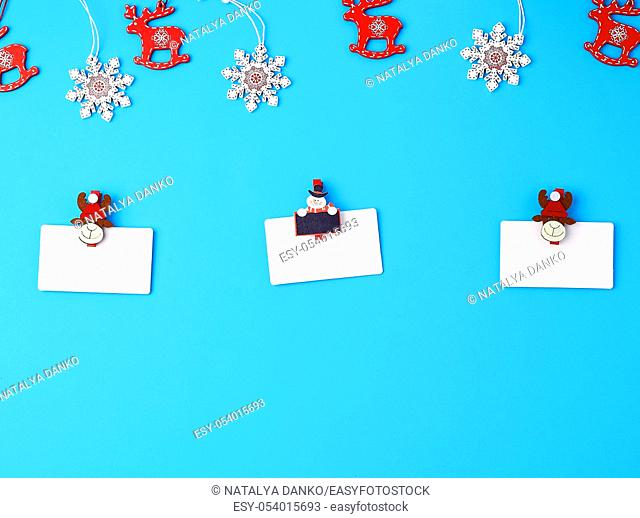 empty white paper business cards and holiday clothespins on a blue background, top view