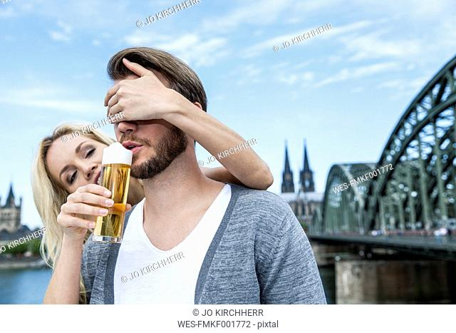 Germany, Cologne, young man tasting Koelsch while his girlfriend covering his eyes