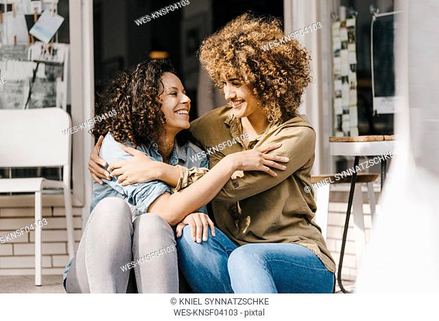 Two laughing friends sitting in front of coworking space, embracing