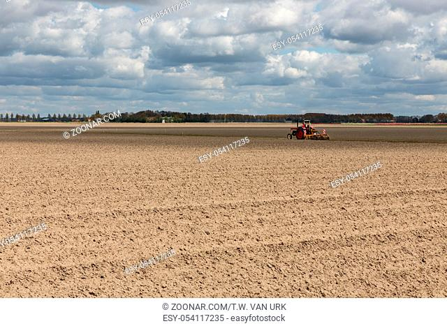 Dutch landscape with tractor in stripes of plowed field in early spring