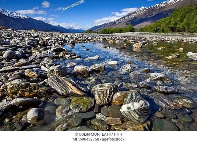 Gneiss stones streaked with quartz on riverbank, Makarora River, Otago, New Zealand