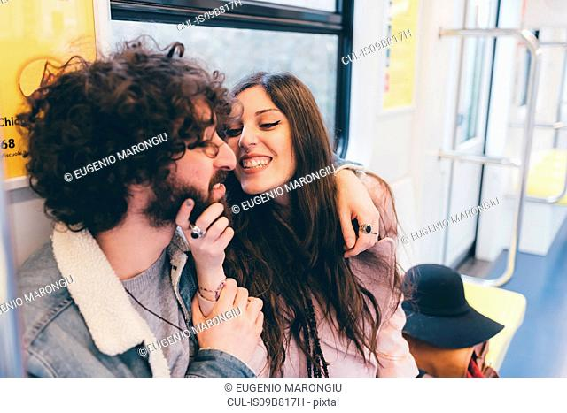 Young couple sitting in subway train, fooling around, woman grabbing man's chin