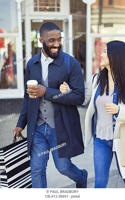 Smiling young couple walking along storefront with coffee and shopping bags
