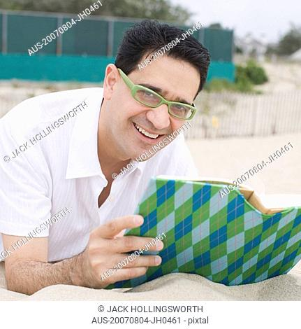 Portrait of a mature man lying on sand and holding a book