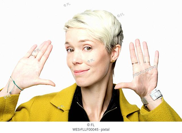 Portrait of smiling woman with short blond dyed hair in front of white background gesturing