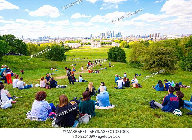 London's National Maritime Museum and skyscrapers of Canary Wharf seen from the hill. Tourists resting on the grass on a beautiful sunny day