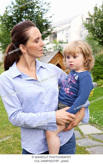 Mother holding daughter in backyard