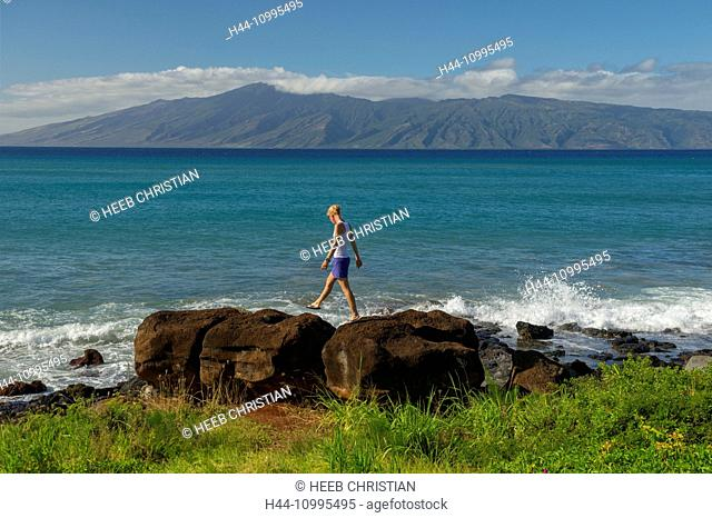 USA, Vereinigte Staaten, Amerika, Hawaii, Maui, Kaanapali, girl walking on cliffs with island of lanai in the background