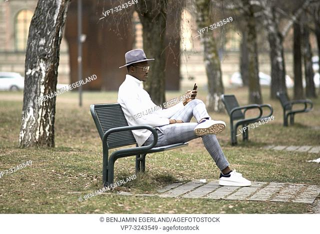 stylish man sitting alone on bench in park, resting, using phone, looking aside, in city Munich, Germany