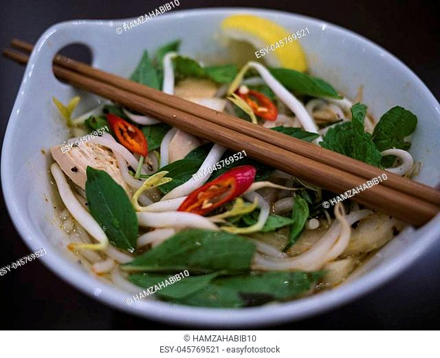 Beautiful and appetizing photo of a traditional vietnamese chicken noodle soup, also know as Pho Ga. In a white bowl with wooden background and luxurious wooden...