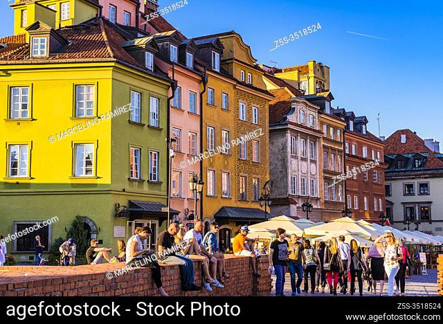 Tourists and locals relaxing in Castle Square at sunset, Old Town. Warsaw, Poland, Europe