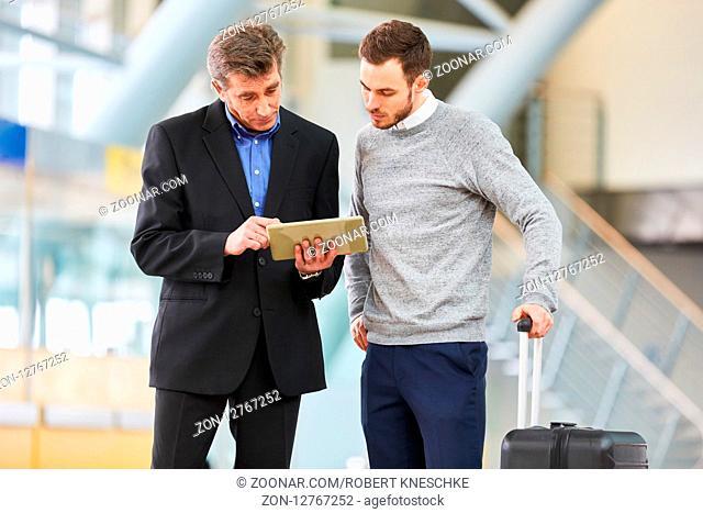 Zwei Business Männer machen Terminplanung für die Geschäftsreise mit Tablet am Flughafen