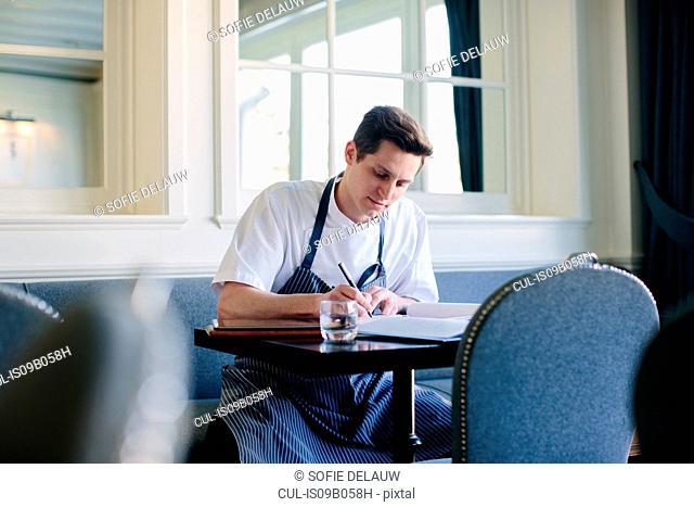 Young male chef writing up menu in restaurant