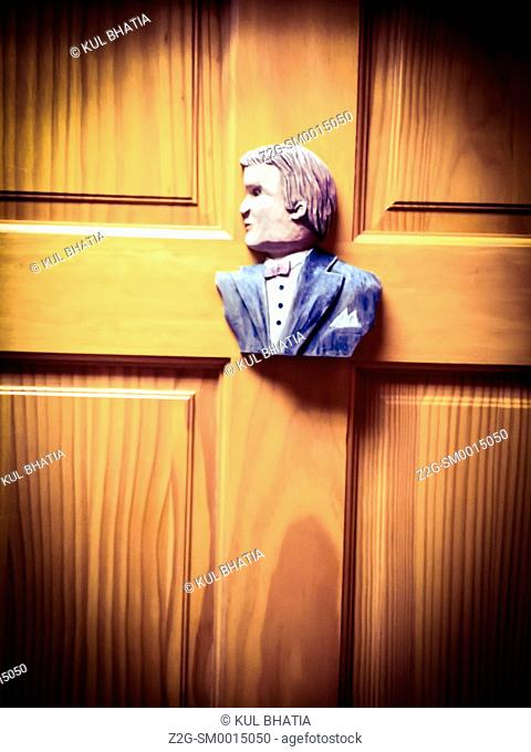 A wood sculpture of a well dressed man on a Men's toilet door, Quebec, Canada