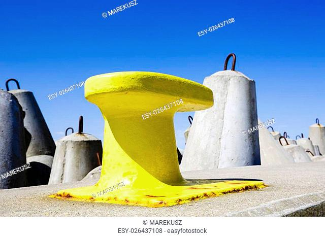 Mooring bollard painted in yellow against the blue sky and large structures made of concrete designed to protect against the big storm waves
