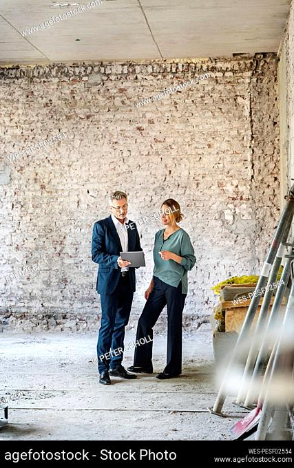 Architect working with colleague over digital tablet while standing at construction site