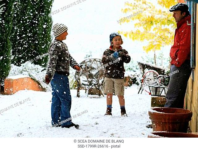 Mid adult man standing with his two sons in snowfall, Provence, France