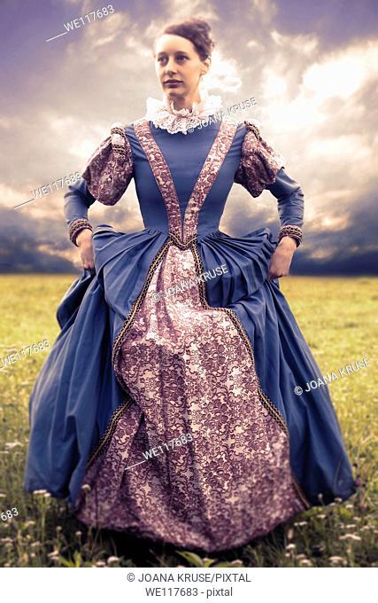a woman in a renaissance dress in a meadow