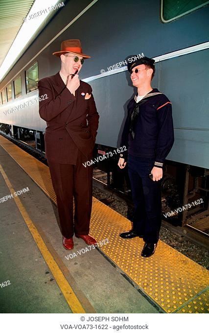 1940's man with pipe and servicemanpose in front of Pearl Harbor Day Troop train reenactment from Los Angeles Union Station to San Diego