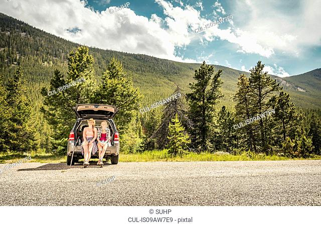 Young woman and teenage girl hiker looking out from car boot, Red Lodge, Montana, USA